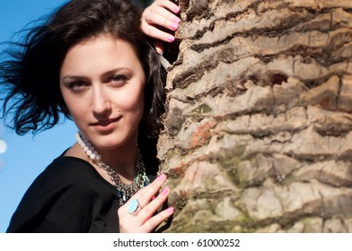 Portrait of a girl behind the palm tree trunk