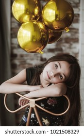 portrait of girl in black dress with gold balls