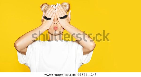 黄色い背景に偽のまつげを手にして、金髪の女の子のポートレート。感情のコンセプト。