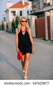 Portrait of a girl blonde in a black dress eyes glasses on the neck of the red beads. Holds a red purse. Natural light solar