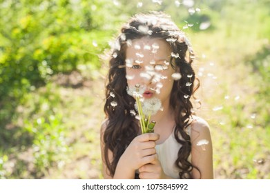 Portrait of girl blowing a dandelion. Beautiful child with dandelion flower in spring park. Happy kid having fun outdoors. Summer wishes. Earth Day
