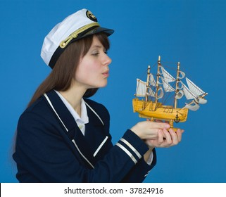 Portrait of the girl blowing on sails of the ship
