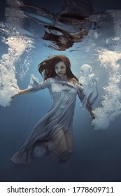 Portrait of a girl in a blue dress under water