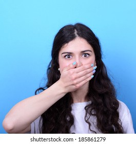 Portrait of girl blushing with hand over mouth against blue background