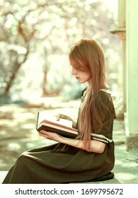 Portrait of a girl with a book. Beautiful teen girl is reading a book outdoors.