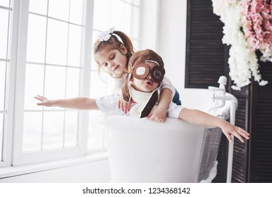 Portrait of a girl and a boy in pilot hat playing in bathroom at pilots or sailors. The concept of travel, childhood and the realization of dreams.