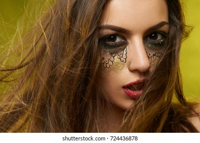 Portrait of a girl with a bright fantastic make-up in black and golden tones, made by an artist. She wears black eyeshadows and burgundy lipstick. Her hair is dark and straight.