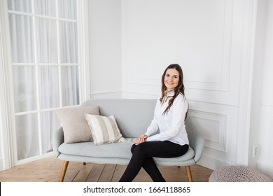 Portrait of a girl in a bright interior, a girl of European appearance sitting on the couch, Manager, freelancer