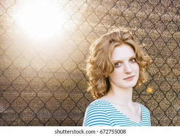 Portrait of a girl by fence with sun