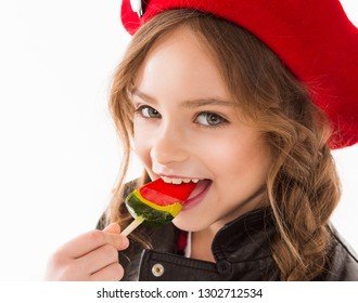 Portrait of a girl with a candy. The child eats candy, face close-up. Happy and fun.