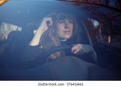 portrait of a girl in a car driver at the wheel
