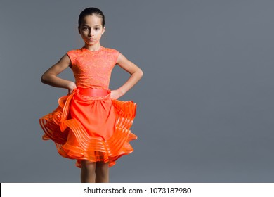 Portrait of a girl child 9-10 years old dancer. Sports ballroom dancing, latino. Girl in an orange dress on a gray studio background, copy space
