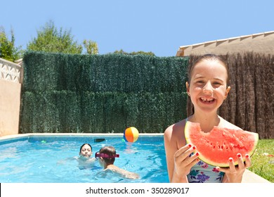 Portrait of girl child smiling eating a slice of watermelon by a swimming pool with joyful children playing in a home garden on a sunny holiday, outdoors. Active kids lifestyle exterior vacation.