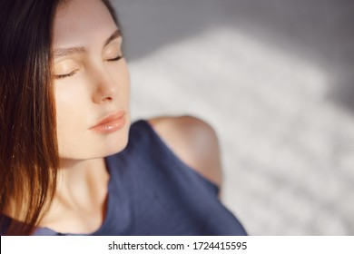 portrait of a girl with closed eyes sitting on a carpet in the morning sun