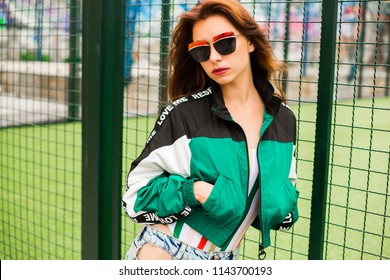 Portrait of a girl clothes in the style of the 90s sports style, jacket, jeans bananas, sunglasses, sports field residential area