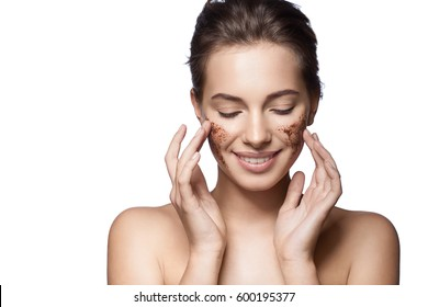 Portrait of a girl with a coffee scrub on her face doing peeling skin isolated on white background