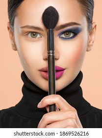 Portrait of a girl with cosmetic brush at face. Woman holds a big makeup brush right in the middle of the face. One half face of a beautiful white woman with  bright makeup and the other is natural.  - Shutterstock ID 1869526216