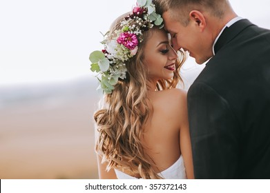portrait of a girl and couples looking for a wedding dress, a pink dress flying with a wreath of flowers on her head on a background chicago garden and the blue sky, and they hug and pose