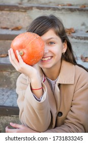 Portrait of a girl covering her eyes with a pumpkin in her hand