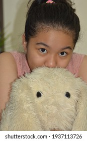 Portrait of a girl cuddling with a furry stuffed toy