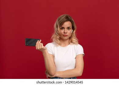 Portrait of a girl with curly blond hair in a white t-shirt on a red background. Model with sceptical look in wireless headset holds mobile phone.