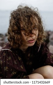 portrait of a girl with curly hair sitting by the water