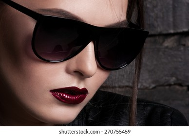 Portrait of girl in dark glasses, with red lips.