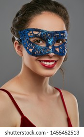 Portrait of girl with dark hair, wearing wine red crop top. The smiling lady is looking at camera, wearing blue carnival mask with perforation, adorned with ladder braid. Vintage carnival accessory.