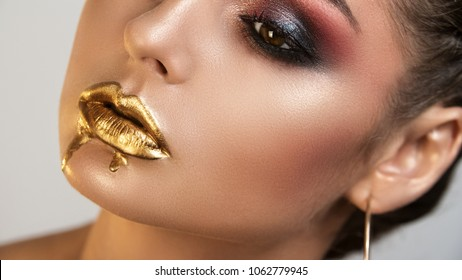 Portrait of girl with  the distinctly painted eyes by a shining skin   by well-groomed eyebrows and liquid gold on lips