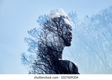 Portrait of a girl with double exposure against a tree crown. Delicate mysterious portrait of a woman with a blue sky