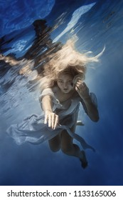 Portrait of a girl in a dress under the water