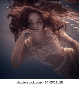 Portrait of a girl in a dress under water
