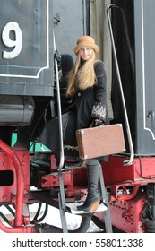 Portrait of a girl dressed in an old train station near the vintage locomotives. Vintage suitcase, retro hats. The style of the last century. Blonde, long hair. Female. Winter.