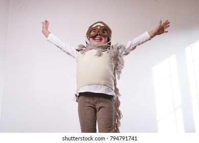 Portrait of a girl, dressed as a pilot or aviator with a hat and glasses, smiles looking at the camera as she dreams with open eyes and thinks about the future. Concept of: success, future, dreams