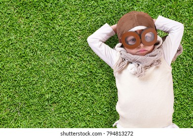 Portrait of a girl, dressed as a pilot or aviator with a hat and glasses, lying in the grass and she dreams with open eyes and thinks about the future. Concept of: success, future, dreams