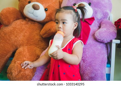 Portrait of girl is drinking milk from a bottle.