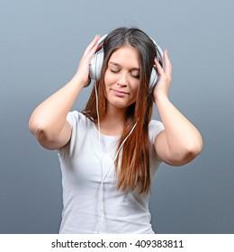 Portrait of girl enjoying her music against gray background