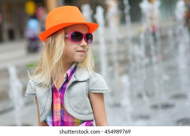 Portrait of girl in fashionable clothes. Elegant Charming cute little girl in sunglasses, orange hat. Fountain in background. Looking to side.