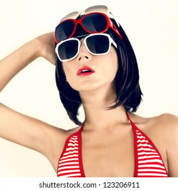 Portrait of a girl in a fashionable swimsuit and sunglasses