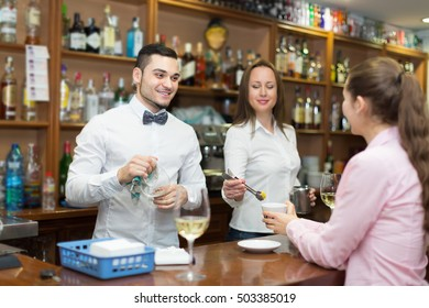 Portrait of girl flirting with handsome young barman at counter