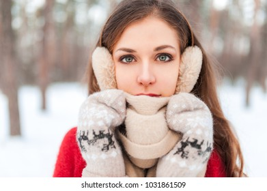 Portrait of a girl in the forest. A girl in mittens, a scarf and warm headphones. Portrait of a man with expressive eyes.