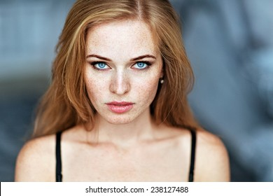 Portrait of a girl with freckles and blue eyes