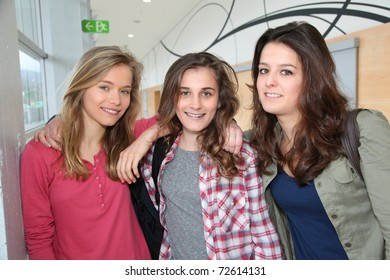 Portrait of girl friends standing in school hall
