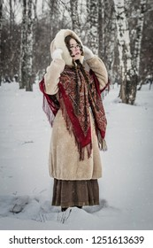 Portrait of a girl in a fur coat on a walk in the park and enjoying a beautiful winter day.