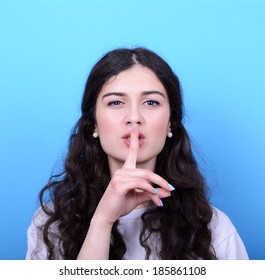 Portrait of girl with gesture for silence against blue background