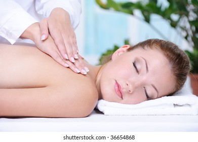 Portrait of girl getting back massage and relaxation in the spa salon