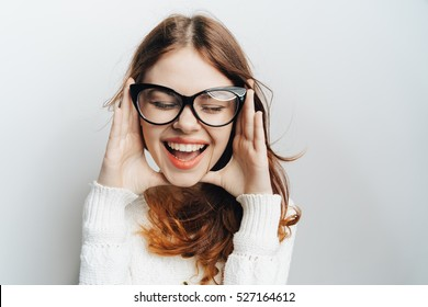 Portrait of a girl in glasses on a light background. Close portrait of a woman with closed eyes and a smile
