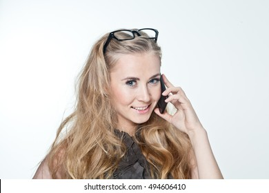 portrait of a girl in glasses with a telephone. Business woman very shrewd and clever in their thoughts and opinions. He decides to do on the phone and learned a lot .
