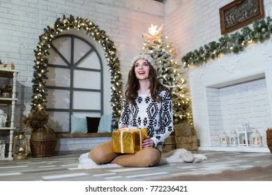 Portrait of girl with golden gift box sitting on the floor in cozy interior