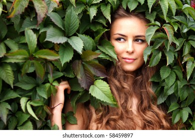 Portrait of the girl in green foliage